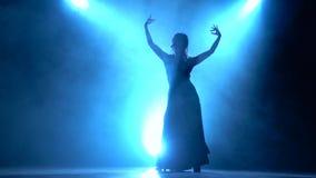 flamenco De danser in de donkere ruimte voert elegante bewegingen met haar handen uit Llight van erachter Rook achtergrond stock footage