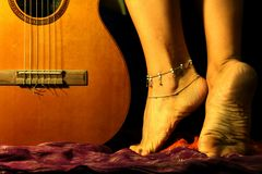 Flamenco dream. Close up of a pair of female feet, nude, with ankle band and spanish guitar Stock Images