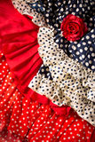 Flamenco dresses in red blue with spot and red rose Royalty Free Stock Photography