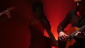 Flamencodansen utförde vid en yrkesmässig flicka bredvid att spela gitarristmusik Ljus bakifrån stora objekt för bakgrundskontrol stock video