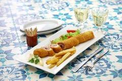 Flamenquin, deep fried long pork roulade, spanish cordoba cuisine. On white background Stock Photos