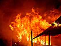Flames. Engulf a structure stock images