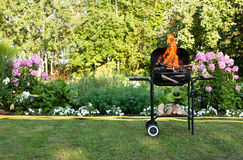 Flames in a barbecue. Flames burning in a barbecue standing in a pretty garden as the coals are prepared for grilling an array of meat for a lunchtime cookout Royalty Free Stock Photography