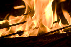 Flames blazing over wooden and grill. Hot fire flames blazing over wooden and grill royalty free stock photo