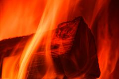 Flames crawl up the side of a single log. Close-up photo of fire in a stove stock images