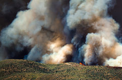 Flames and Dense White Smoke Rising from the Raging Wildfire Royalty Free Stock Photo