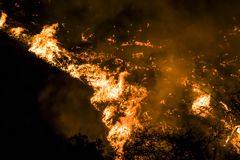 Close up Flames and Embers at Night Twist into Tornado Shape During California Fire. Flames and embers twist into tornado shape burning hillside at night during stock photo