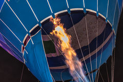 Flames Filling a Hot Air Balloon. Flames shooting inside a hot air balloon filling it with air getting ready for a launch Stock Image