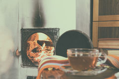 Flames of fire in a fireplace and cup of tea Stock Image