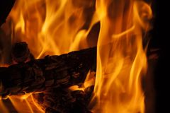Trunk burning in the fireplace with large flames. Flames of fire in the fireplace with a pot put warm royalty free stock photos