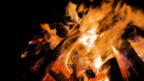 Flames of fire place lit the bonfire night sparks smoldering logs and falling snow close-up shot stock footage