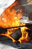 Flames in the fireplace. Hot burning wood and flames in the fireplace. Campfire Stock Photography
