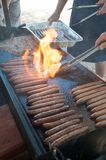 Flames flaring up on the hot plate with sausages and onions stock image