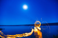 Flames over water at night. Stock Images