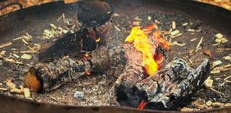 Flames,pot,burning,burning wood,ash. Large pot containing burning wood with flames Stock Image