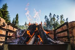 Flames rising beautifully into clear blue sky from logs burning royalty free stock photos