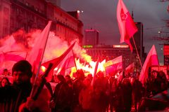 Independence Day March in Warsaw Poland Marred by Violence and Controversy. Flames and smoke emanate from flares as protesters wave flags at the annual Polish Royalty Free Stock Image