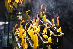Flames and smoke of yellow burning candles in buddhist temple, Chiang Mai, Thailand stock images