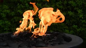 Flames swaying in a decorative outdoor fire pit. stock video