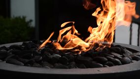 Flames swaying in a decorative outdoor fire pit.  3 stock footage