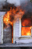 Flames in window and door. House fully involved in flames Royalty Free Stock Photos
