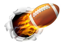 Flaming American Football Ball Tearing a Hole in the Background Royalty Free Stock Images