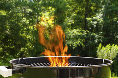 Flaming Barbeque Charcoal Grill. Fire flames in a BBQ charcoal grill after igniting the charcoal briquettes in the grill. Shallow DOF focus on the back of the Stock Image