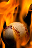 Flaming baseball. A weathered baseball engulfed in flames Stock Image