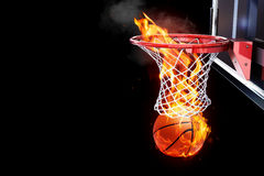 Flaming basketball going through a court net.