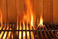 Flaming BBQ Charcoal Cast Iron Grill And Wood Background. Flaming BBQ Charcoal Cast Iron Grill Close-up And Brown Wood Siding Wall In  The Background. Cookot or Royalty Free Stock Images
