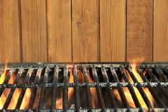 Flaming BBQ Charcoal Cast Iron Grill And Wood Background. Flaming BBQ Charcoal Cast Iron Grill Close-up And Brown Wood Siding Wall In  The Background. Cookot or Stock Images