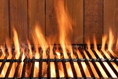 Flaming BBQ Charcoal Cast Iron Grill And Wood Background Royalty Free Stock Photography