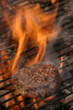 Flaming burger. Burger on a grill with steam and fire around it Stock Images