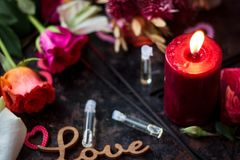 Flaming candle and perfume in glass bottles. Flaming candle and perfume in glass bottles Stock Image