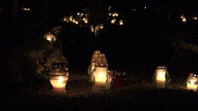 Flaming candles on the grave on All saints day at night. Focus change. 4K stock video