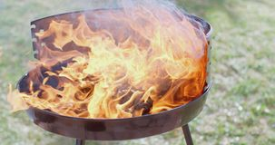 Flaming charcoal briquettes in a BBQ stock video footage