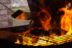 Flaming grill. Quickly Flipping & pressing burgers on a grill showing motion blur Stock Images