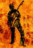 Flaming Guitarist With Electric Guitar. A rock and roll guitarist walking through the fires of Hell Stock Photography