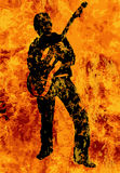Flaming Guitarist With Electric Guitar. A rock and roll guitarist walking through the fires of Hell Royalty Free Stock Image