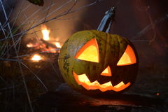 Flaming halloween pumpkin head jack with fire on the background. In dsrk forest Royalty Free Stock Images