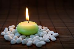 Flaming harmony. Composition with white zen stones and burning candle, symbolizing harmony, calmness and relaxation. On dark background Royalty Free Stock Photos