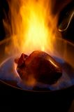 Flaming heart. Flaming pork heart on a pan Royalty Free Stock Photography