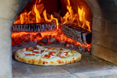 Flaming Hot Wood Fired Pizza Baking Oven. Flaming Hot Wood Fired Pizza Baking in an Oven Royalty Free Stock Photography