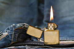 Flaming lighter. And blue jeans Royalty Free Stock Images