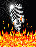 Flaming microphone. Retro microphone burining in the flames Royalty Free Stock Photo