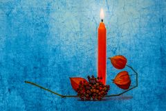 Flaming orange candle, branch of cape gooseberry Stock Photo