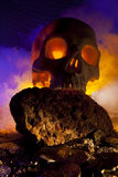 Flaming Skull and Gold Coins Stock Photo