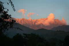 Flaming sunset over snowpeaked  himalayan ranges Stock Photos