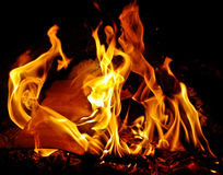 Flaming wood fire at night. A closeup view of bright orange flames from a wood fire at night Stock Image