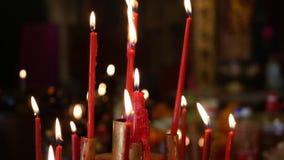 Flamma från att bränna röda stearinljus i kinesisk släkt- tempel 4K lager videofilmer